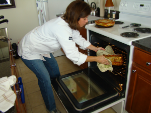 Dianne taking lasagna from the oven